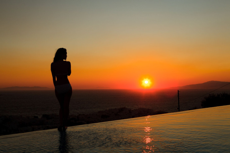 A beautiful lady standing on the luxury hotel swimming pool views